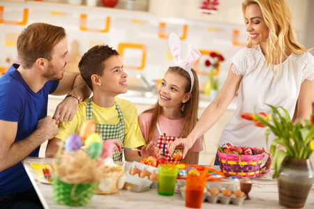 Smiling woman with family preparing Easter basket with colorful eggs