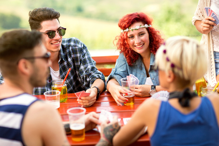 Group of young in nature plays cards, talks and drink beverage
