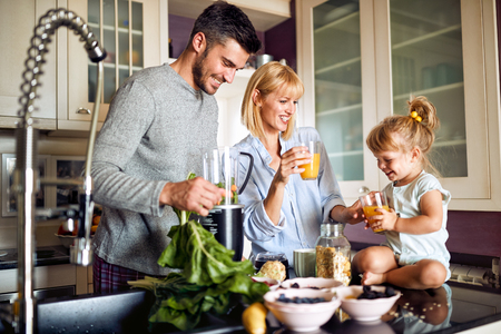 Cheerful family with daughter having breakfast