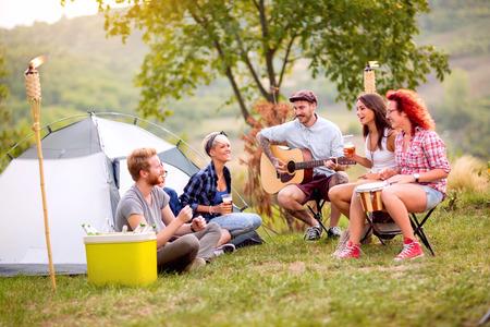 Gruppo di giovani che si rilassano e si divertono davanti alla tenda
