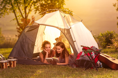 Two girls on camping trip lying in tent and reading book Stock Photo
