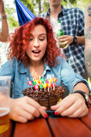 Portrait of young curly red haired girl with little blue birthday cap and chocolate cake in nature