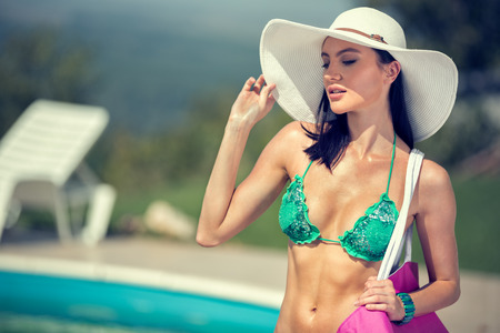 Glamorous woman with summer hat in backyard