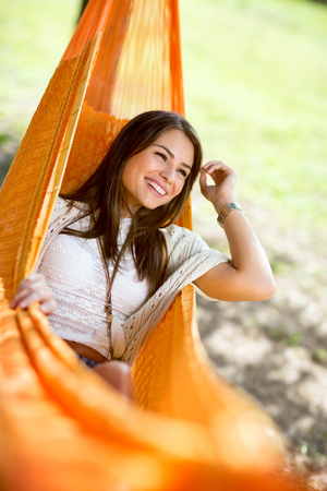 Young cute girl enjoy in orange hammock in woods