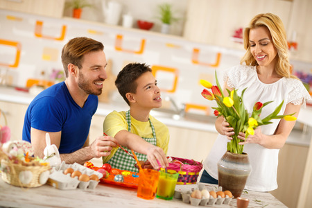 Father with son coloring Easter eggs while mother arranges tulips in vase Stock Photo