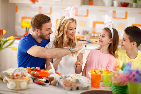 Father having fun with daughter while painting Easter eggs Stock Photo