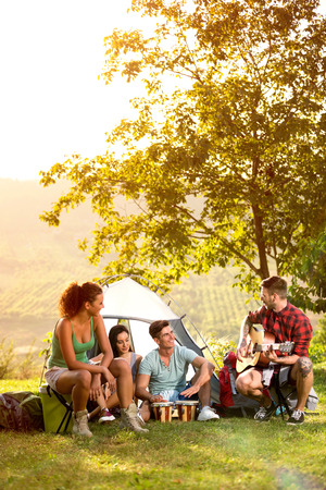 young people on camping trip to play and sing, relaxing on vacation Foto de archivo - 121569326