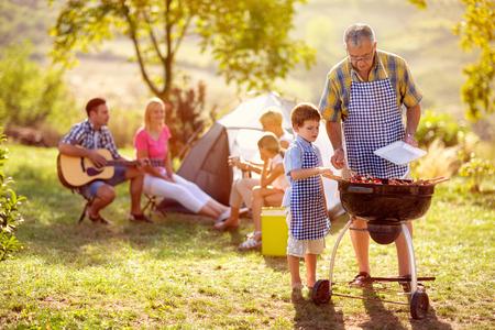 kleinzoon koken op kampvuur met grootvader op camping