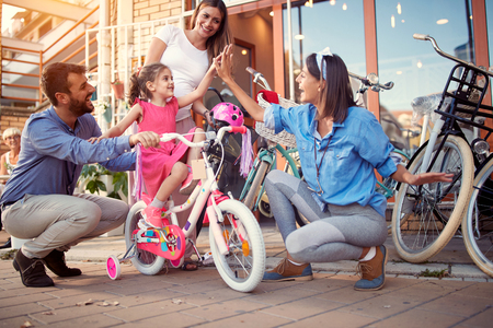 Selling bicycle - Young family buy new bicycle for happy little girl in bike shop Stock Photo - 121569420