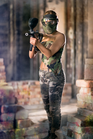 Attractive woman paintball player with gun and mask