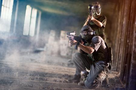 Equipo de paintball juntos disparando con ropa de camuflaje Foto de archivo