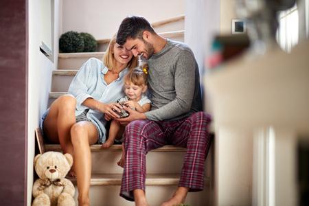 Mamá y papá con niño adorable divirtiéndose en las escaleras Foto de archivo