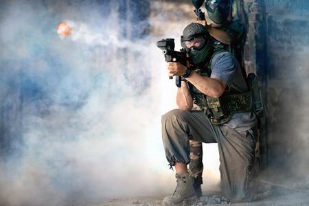 Disparo del equipo de paintball, defendiendo la acción