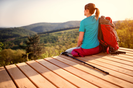 Young girl with backpack sitting and looking nature, back view