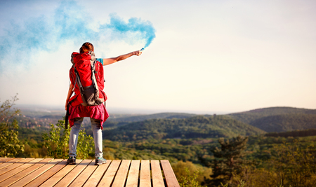 Young girl hiking and showing smoke signals torch