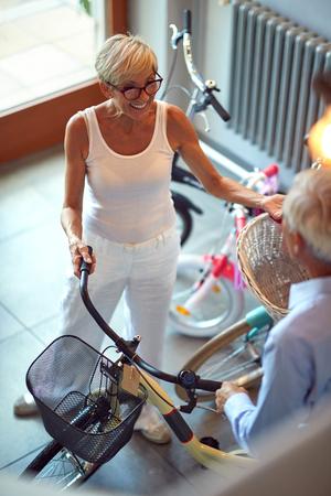 Smiling family senior couple choosing new bicycle in bike shop