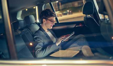 modern businesswoman working late in car in back seat