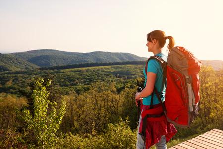 Teenage hiker female standing up and looking panorama Banco de Imagens