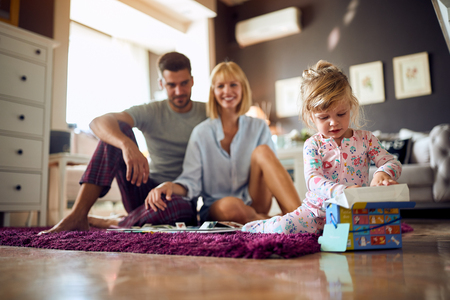 Female child and parents playing in the morning in room