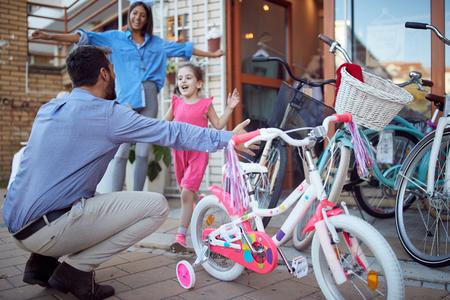 Young family enjoying shopping new bicycle in bike shop