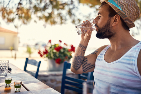 Young man hipster relaxes and drinking on vacation