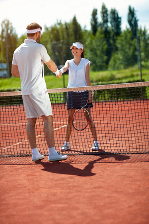 Girl with tennis trainer shaking hands on tennis court