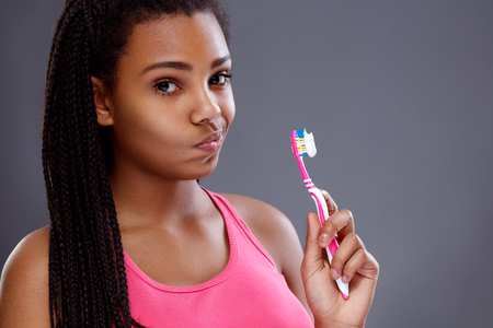 African girl doesn't want to brush her teeth, concept