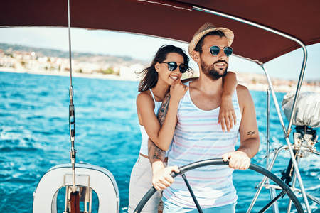 Romantic young couple on a yacht enjoy bright sunny day on vacation