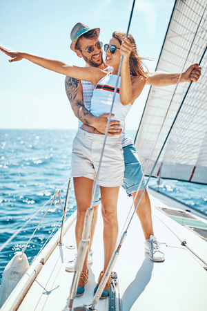 Young smiling man with girl on a sailing boat -Romantic vacation and luxury travel.