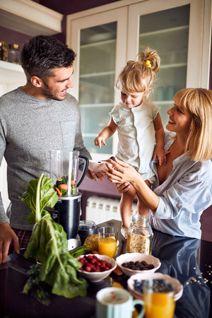 Happy parents giving to daughter healthy breakfast
