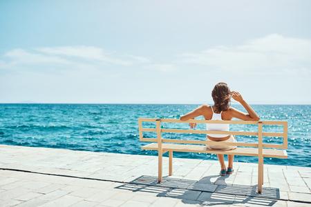 Jeune femme séduisante sur le banc pendant les vacances d'été
