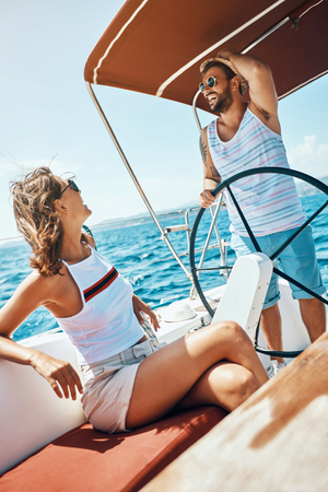 Romantic vacation and luxury travel -Happy young man and woman on a sailing boat