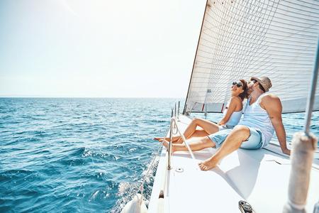 Junger Mann und Frau, die sich im Sommer auf einer Yacht entspannen. Standard-Bild
