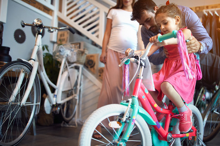 Young family buying new bicycle for happy little girl in bike shop