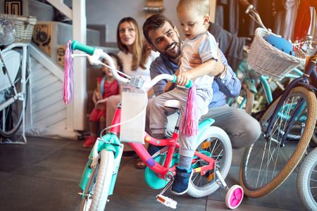 Father buying new bicycle for happy boy in bike shop