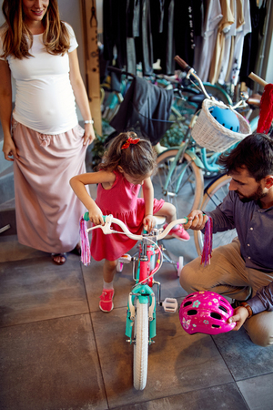 Young father and mother choice new bicycle for happy little girl in bike shop top view