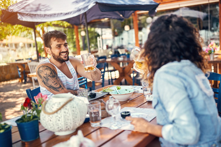 Smiling loving couple sitting in a restaurant enjoying in beer and conversation