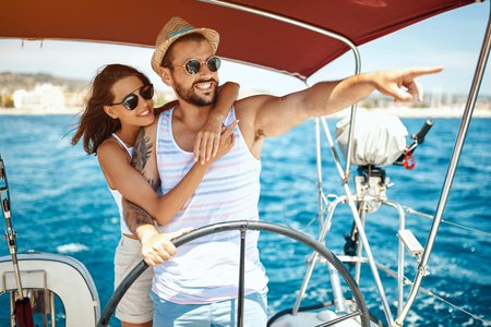 Beautiful young couple of lovers sailing on a boat and enjoy bright sunny day