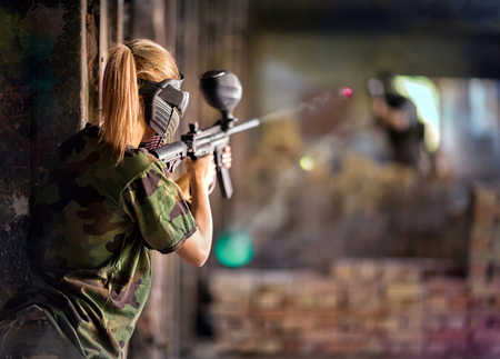 Paintball  player in action behind cover during shootout