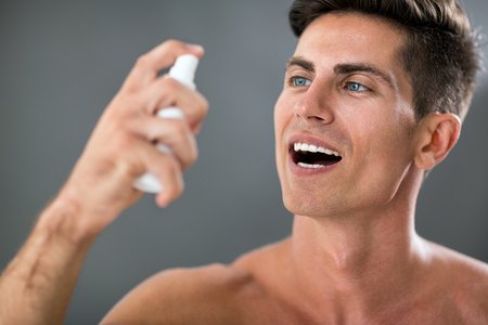 Attractive man applying fresh breath spray
