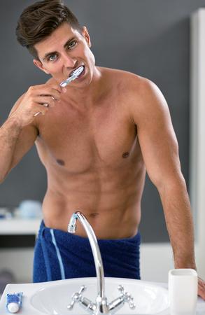 Man in bathroom brushing teeth front of mirror