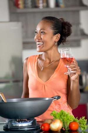 Smiling young woman in kitchen with glass of wine