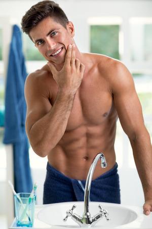 beau jeune homme dans sa salle de bain examine son visage, touchant sa barbe Banque d'images