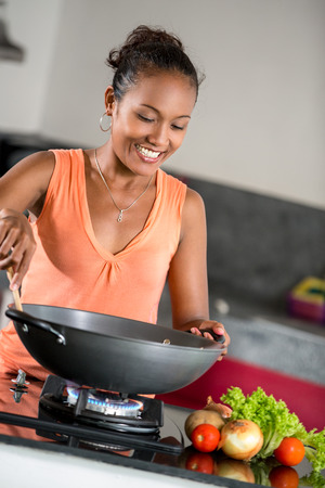 young woman in the kitchen preparing food in the wok