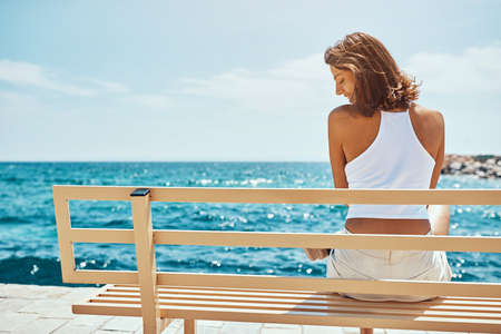 Happy attractive woman on the bench during summer vacation