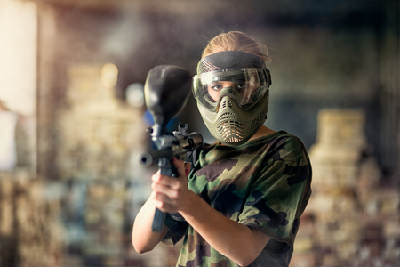 Female paintball player with mask targeting in camera