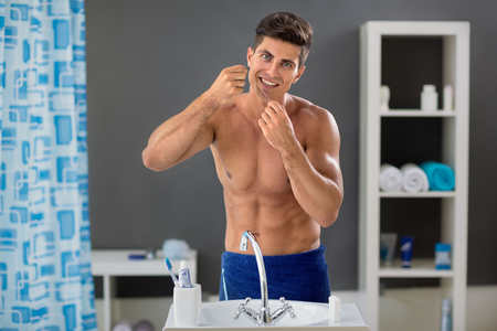 young man cleaning his teeth with dental floss and smiling while standing in front of the mirror