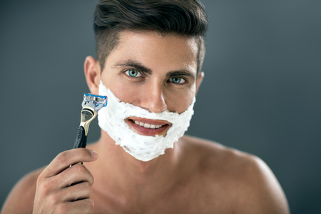young man shaving his beard with razor front of mirror Archivio Fotografico