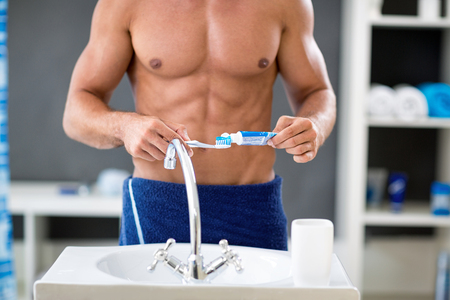 shirtless man squeezes the toothpaste, dental hygiene Stock Photo