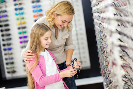 Young mother with lot of patience helps her girl to choose good frame for eyeglasses